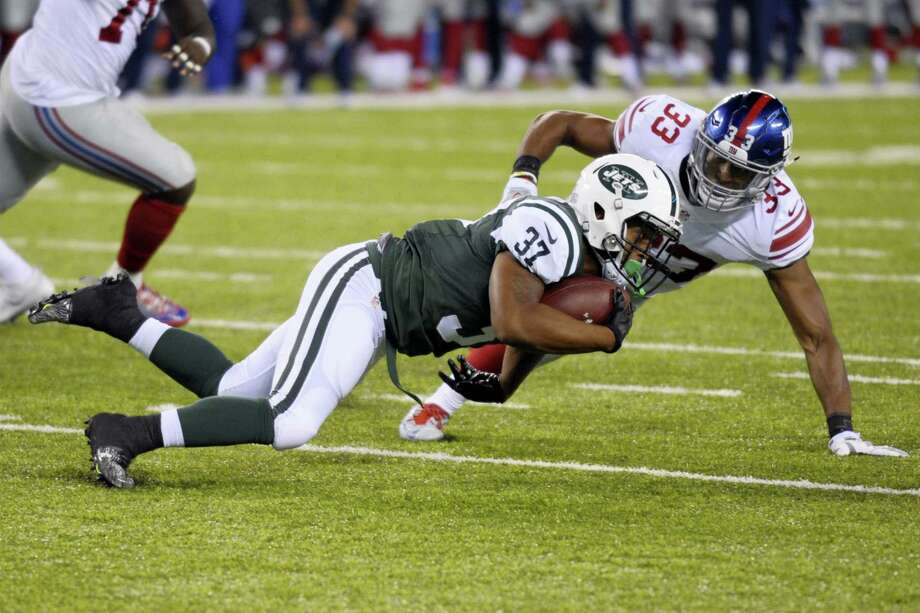 The Giants' Andrew Adams (33) tackles the Jets' Bryson Keeton during the second half on Saturday. Photo: Bill Kostroun — The Associated Press   / FR51951 AP