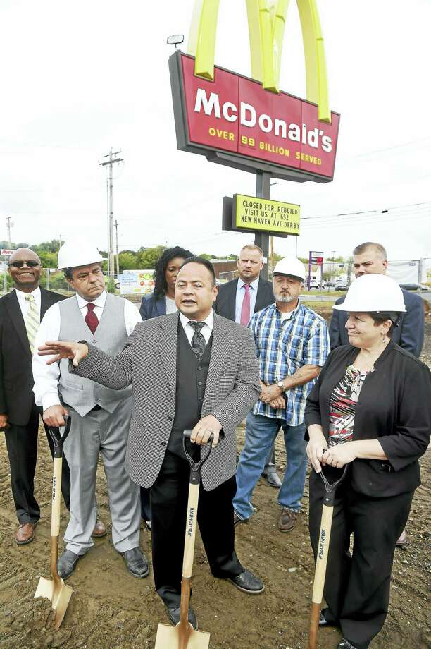 (Arnold Gold-New Haven Register)  Left to right in hardhats, Ansonia Mayor David Cassetti, former Derby Mayor Anthony Staffieri and Derby Mayor Anita Dugatto listen to McDonald's owner Joe Rodriguez (center) talk about the new modern and expanded McDonald's being built at this location on Division St. in Derby during a groundbreaking ceremony on 9/27/2016. Photo: Journal Register Co.