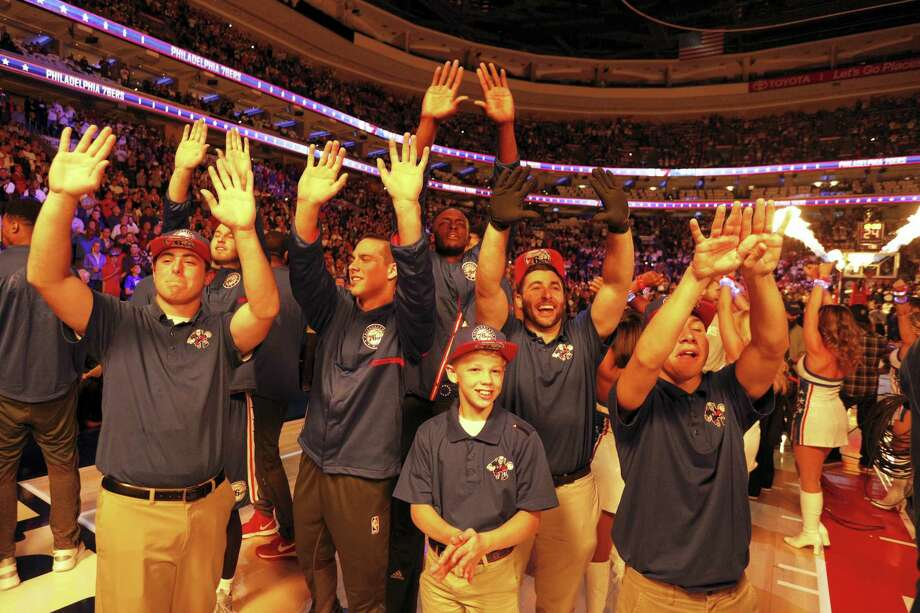 Members of the 76ers and staff warm themselves with the flames from the pyrotechnics prior to an NBA basketball game against the Oklahoma City Thunder, Wednesday, Oct. 26, 2016, in Philadelphia. The Thunder won 103-97. Photo: AP Photo/Chris Szagola    / FR170982 AP