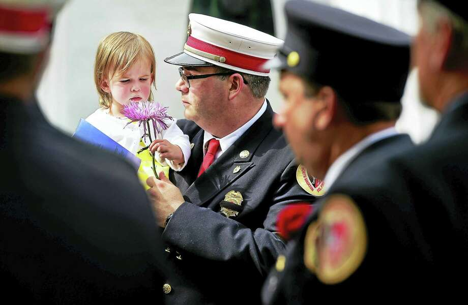 Chris Bernier holds his daughter Arabella, 1, after the funeral of his wife, North Madison Volunteer Fire Company firefighter Amanda Bernier, 32 , at the North Madison Congregational Church Tuesday. Bernier died battling ALS. Photo: Peter Hvizdak - New Haven Register   / ©2016 Peter Hvizdak