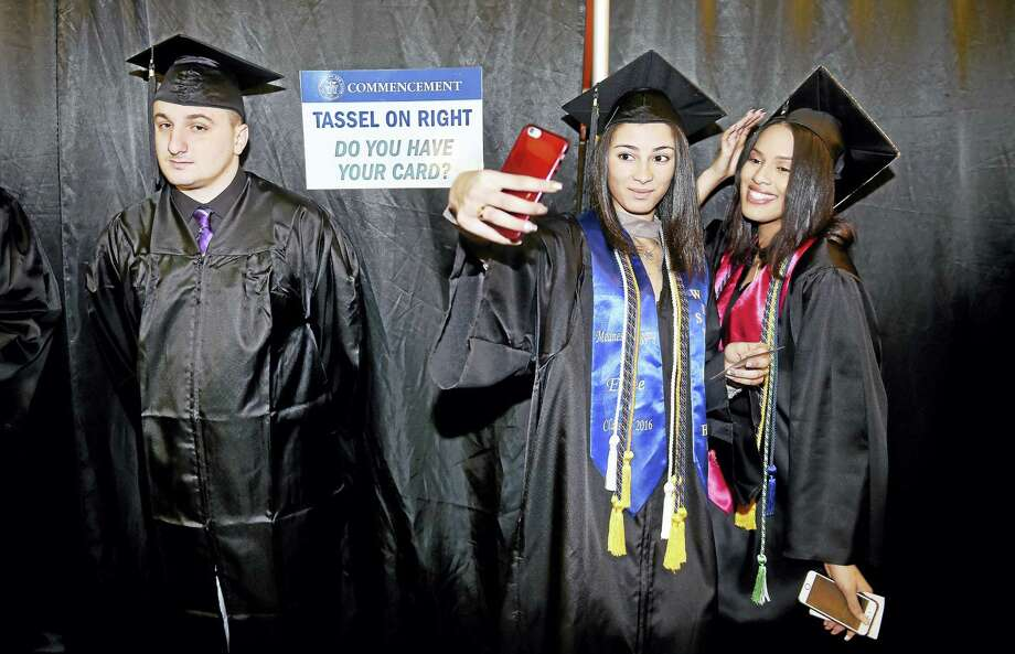 Zoraida Ferguson, center, and Donejia Somerville take a selfie before commencement exercises begin for the University of New Haven at Toyota Oakdale Theatre in Wallingford Sunday.  At left is Thomas Sorbella. The three received a bachelor of science degree from the Henry C. Lee College of Criminal Justice and Forensic Sciences. Photo: Arnold Gold-New Haven Register
