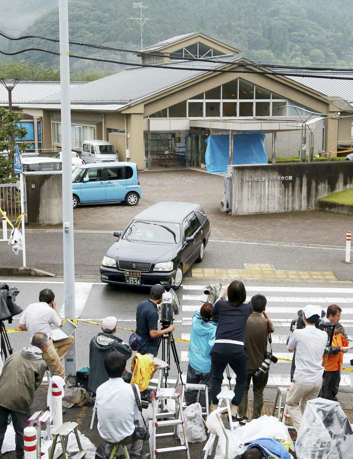 A hearse leaves the Tsukui Yamayuri-en, a facility for the mentally disabled where a number of people were killed and dozens injured in a knife attack Tuesday, July 26, 2016, in Sagamihara, outside Tokyo. A young Japanese man went on a stabbing rampage early Tuesday at the facility where he had been fired, officials said, killing many people months after he gave a letter to Parliament outlining the bloody plan and saying all disabled people should be put to death.