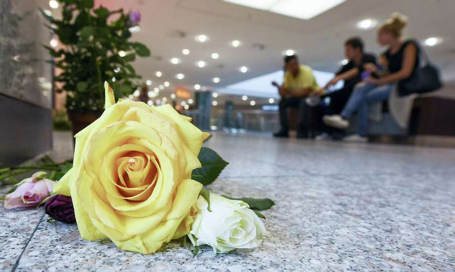 Flowers lie on the ground in the Olympic shopping mall (OEZ) four days after a shooting that killed and injured several people in Munich, Germany, Tuesday July 26,  2016. An 18-year-old German-Iranian fired the shots in a deadly rampage at the Munich mall. Photo: Sven Hoppe/dpa Via AP    / dpa