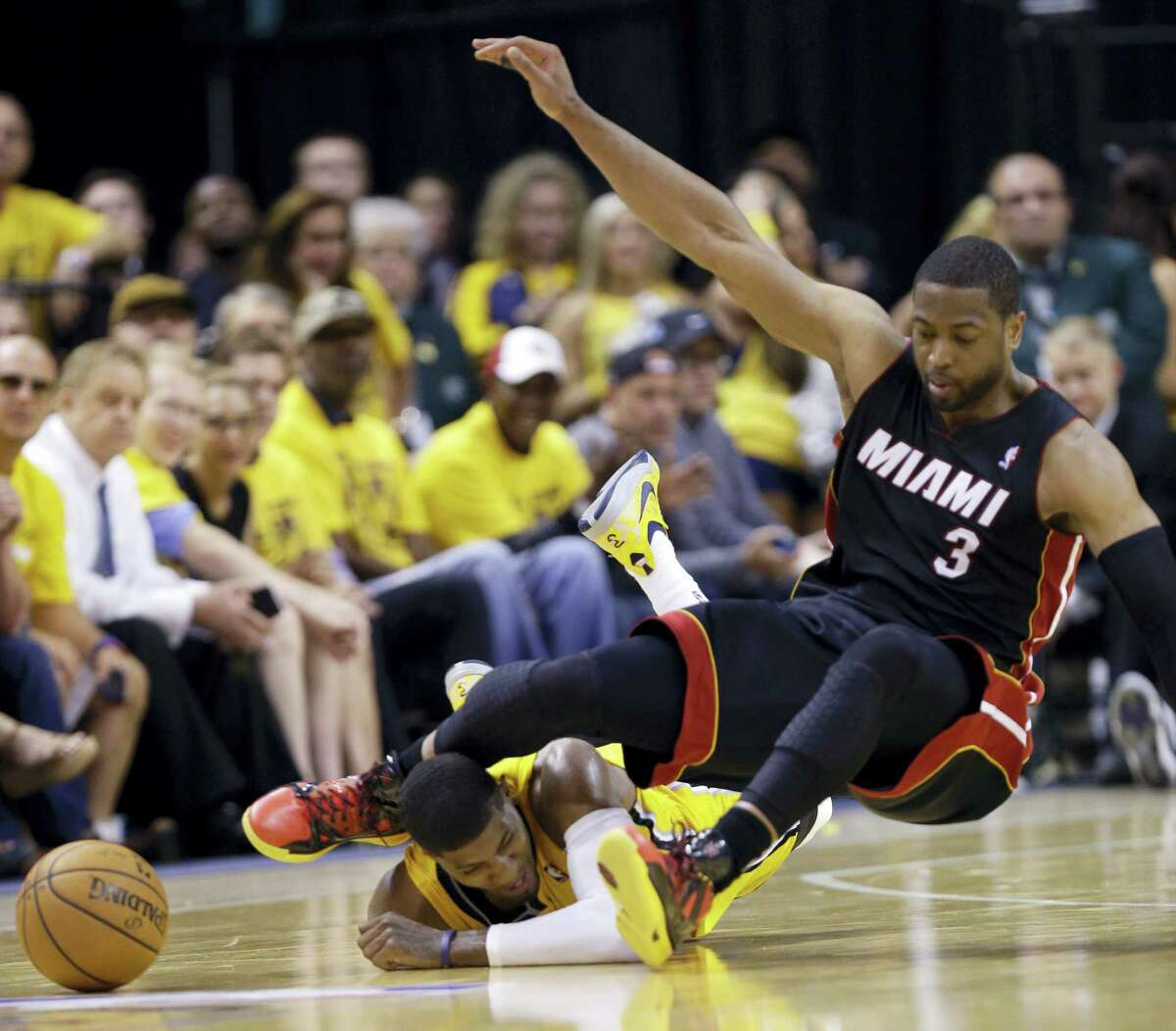 In this May 20, 2014 photo, Indiana Pacers forward Paul George lies on the floor as the knee of Miami Heat guard Dwyane Wade (3) makes contact with his head as they went for a loose ball during the fourth quarter of Game 2 of the NBA basketball Eastern Conference finals in Indianapolis.