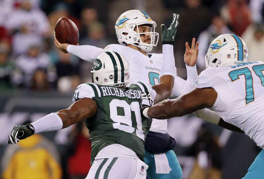 Dolphins quarterback Matt Moore (8) throws under pressure from Jets defensive end Sheldon Richardson on Saturday. Photo: The Associated Press    / FR110666 AP