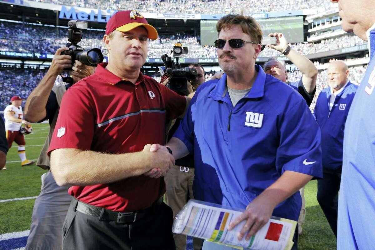 Washington head coach Jay Gruden, left, and Giants head coach Ben McAdoo, right, shake hands after Sunday's game.