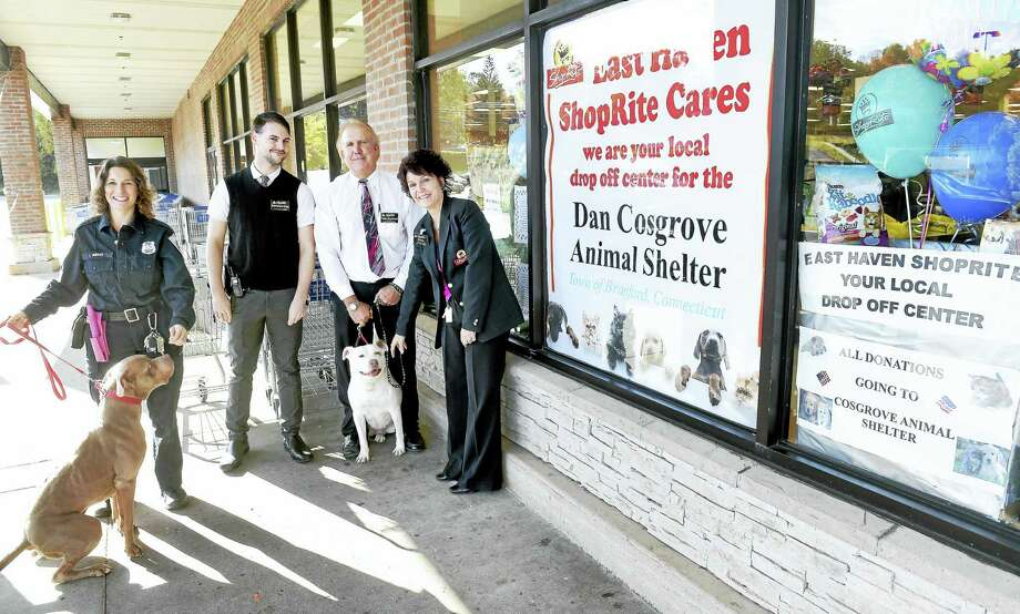 From left, Laura Burban, director of the Dan Cosgrove Animal Shelter; Matthew Gray, grocery manager; Todd Emanuel, store manager; and Dawn Iadarota, customer service manager, are photographed with Hooch, left, and Ruby, center, in front of the East Haven ShopRite, where donations are being collected for the shelter. The two dogs currently are up for adoption, along with many other animals, at the Branford shelter. Photo: Arnold Gold — New Haven Register