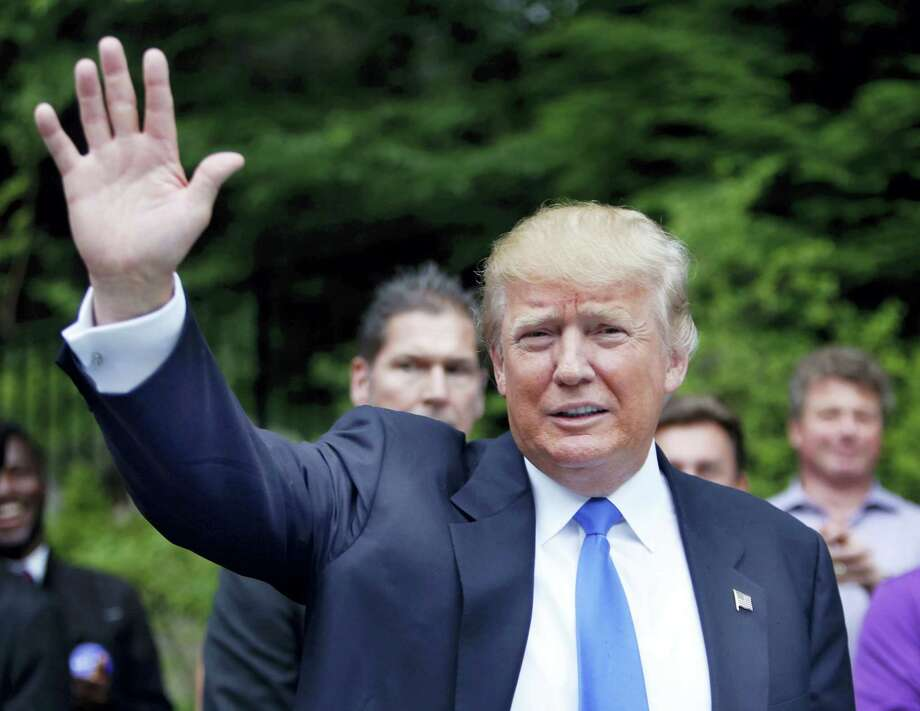 In this June 30, 2015, photo, Republican presidential candidate Donald Trump waves as he arrives at a house party in Bedford, N.H. Hispanic leaders are warning of harm to Republican White House hopes unless the party's presidential contenders do more to condemn Trump, who's refusing to apologize for calling Mexican immigrants rapists and drug dealers.  (AP Photo/Jim Cole) Photo: AP / AP