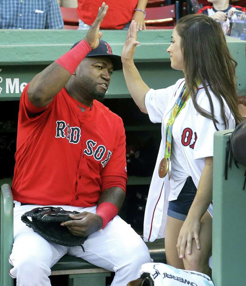 David Ortiz, left, high-fives with Aly Raisman, U.S. Olympic gold medalist in gymnastics, before she threw a ceremonial first pitch prior to Friday's game. Photo: Elise Amendola — The Associated Press   / AP