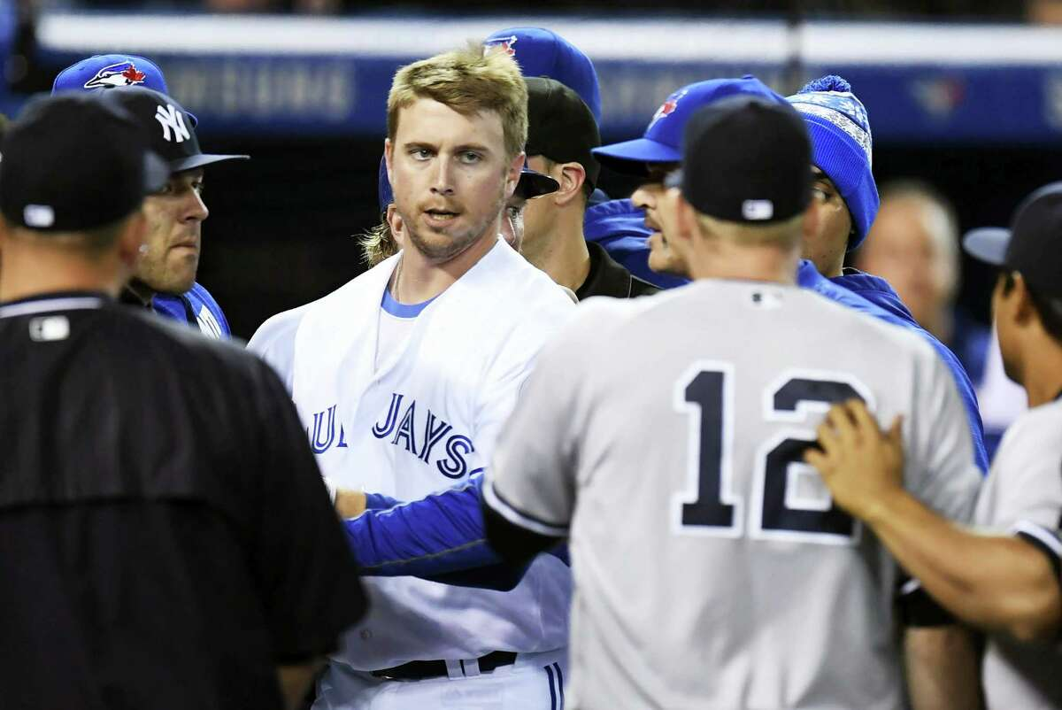 The Blue Jays' Justin Smoak looks at the Yankees' Chase Headley during a bench-clearing melee in the second inning.