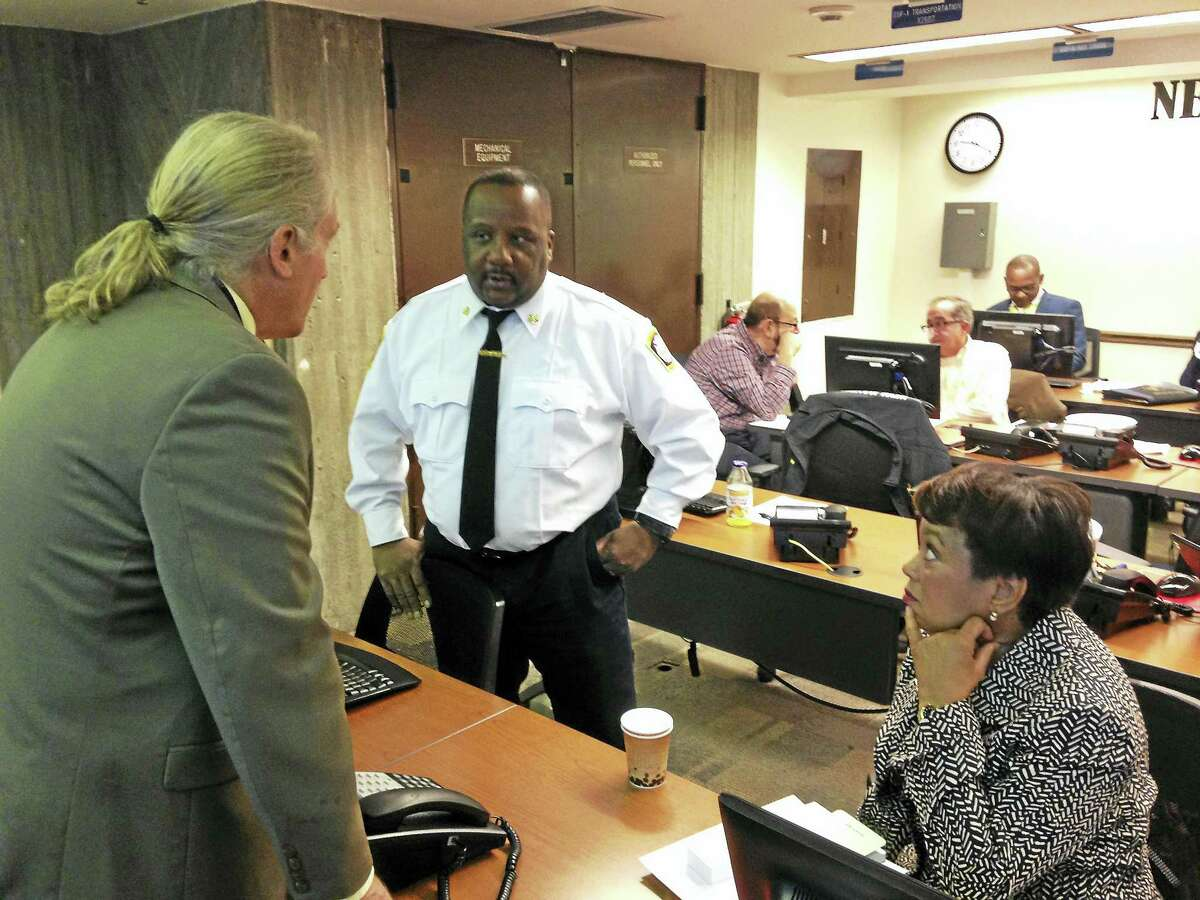New Haven emergency operations staff and partners preview winter weather operations during a dry run Wednesday at the Emergency Operations Center. Here, Mayor Toni N. Harp, seated, speaks to New Haven Fire Chief John Alston, second from left, and Harp's City Hall spokesman, Laurence Grotheer, left.