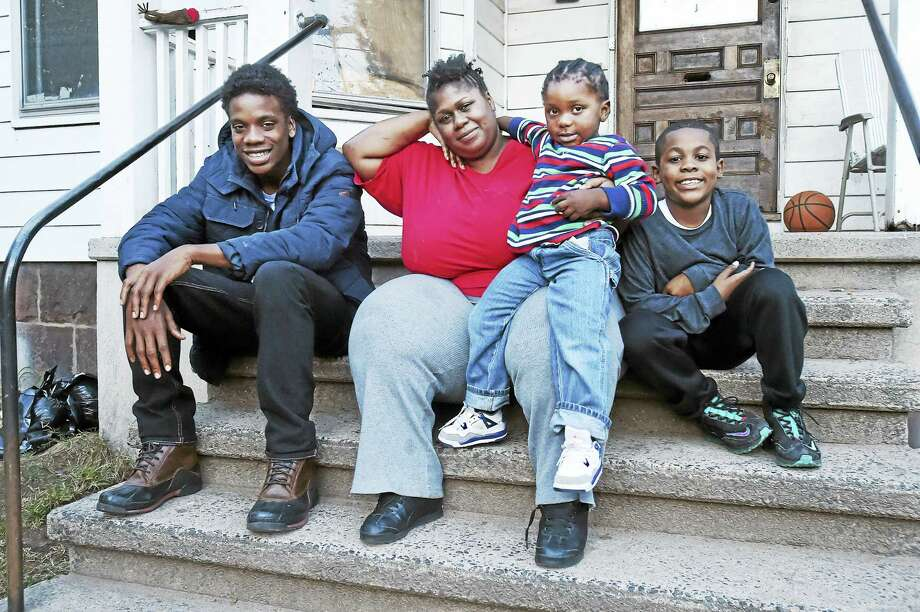 Latasha O'Bryan and three of her four sons, Ja-Sen Smith, 16, Jamyl Mercer, 3,  and Isaiah Staton, 9, on the front porch of her parents' New Haven home Wednesday. O'Bryan's son Kenneth Watts, also 16, is not pictured. Photo: Catherine Avalone — New Haven Register   / New Haven RegisterThe Middletown Press