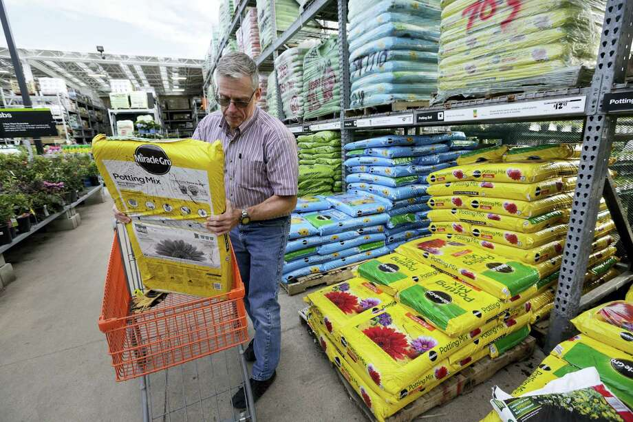 In this Wednesday, May 18, 2016, photo, Joe Russo, of Medway, Mass., puts a bag of potting soil into a cart while shopping at a Home Depot store location, in Bellingham, Mass. The U.S. economy expanded at a sluggish pace this spring as businesses sharply reduced their stockpiles of goods and spent less on new buildings and equipment, according to information released by the Commerce Department, Friday, Aug. 26, 2016. Photo: AP Photo/Steven Senne    / Copyright 2016 The Associated Press. All rights reserved. This material may not be published, broadcast, rewritten or redistribu