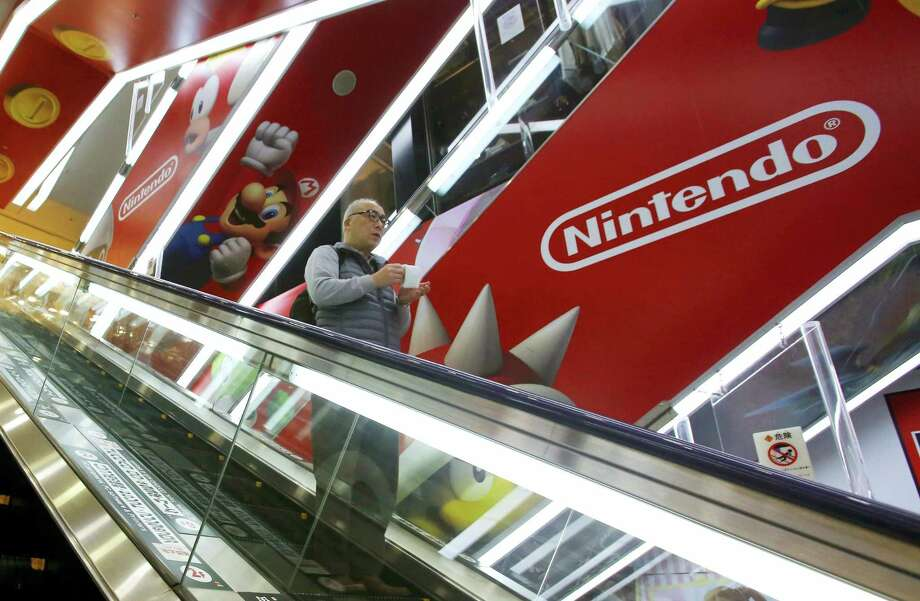 A shopper on an escalator passes by the Nintendo logo at an electronics store in Tokyo. Photo: AP Photo/Shizuo Kambayashi, File   / Copyright 2016 The Associated Press. All rights reserved. This material may not be published, broadcast, rewritten or redistribu