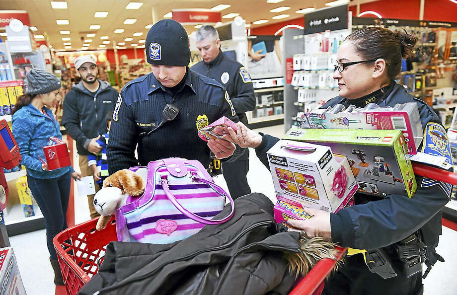 Ansonia Police Detective Richard Esposito, center, and Sgt. Jenifer Guisto, right, scan the prices of toys for Ivania Santos, far left, and her children at Target in Ansonia on 12/17/2016. The Ansonia Police Department raised money and gave Target gift cards to eight families who needed help with holiday shopping. Photo: Arnold Gold — New Haven Register