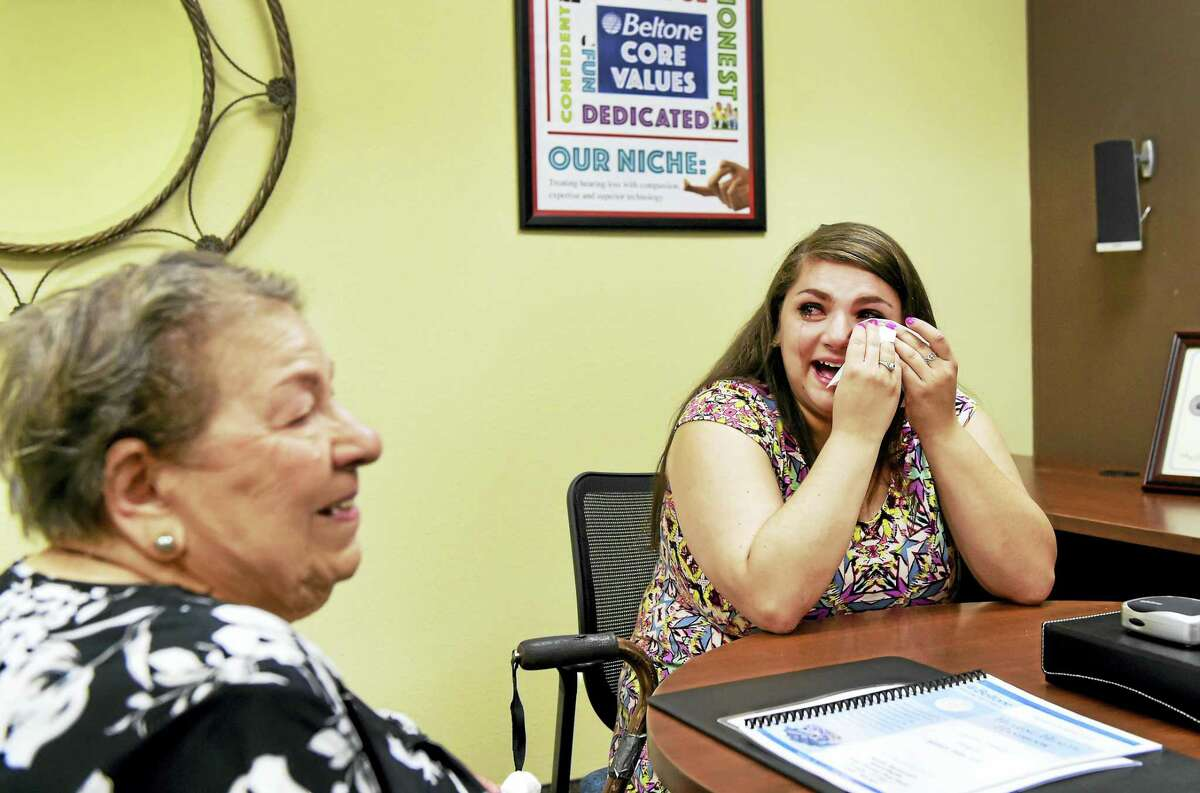 Loretta D'Aniello, 91, of West Haven, left, after being fitted for a Beltone BTE hearing aid, and D'Aniello's granddaughter, Melissa D'Aniello, right, cry together after Loretta realizes she can hear clearly Tuesday at the Beltone Hearing Center in Orange.