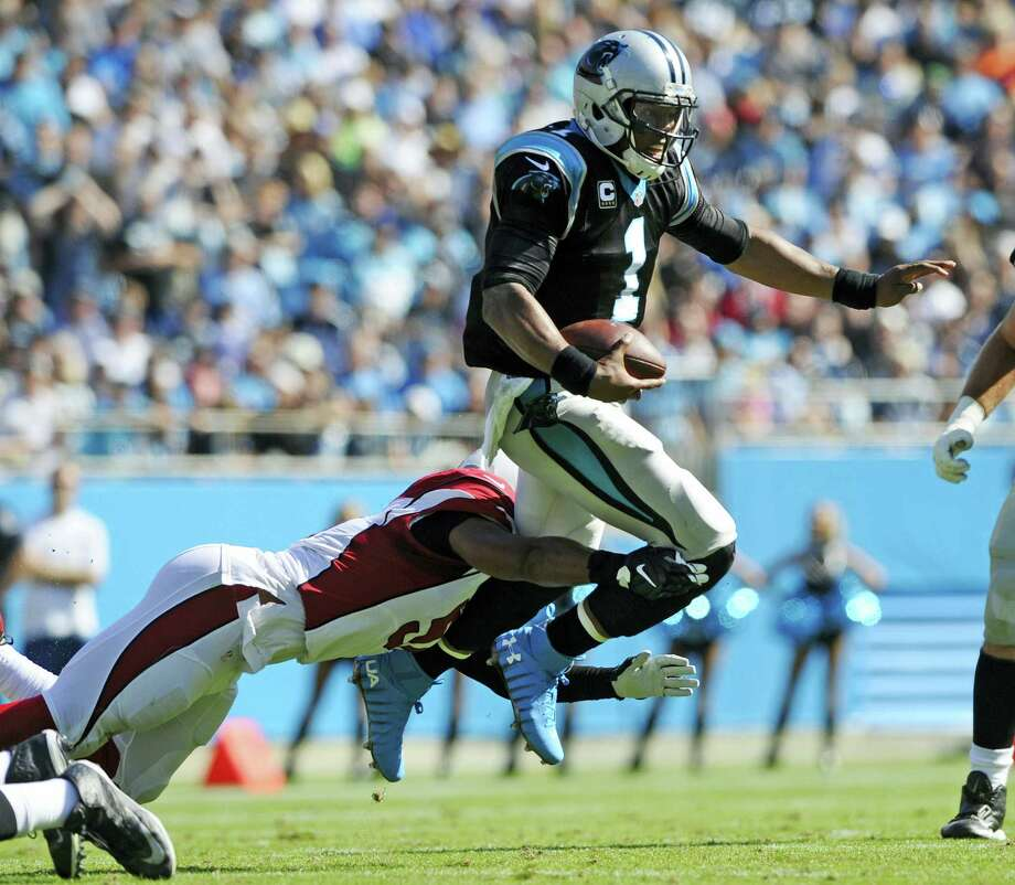 Carolina Panthers' Cam Newton (1) leaps to avoid the tackle of Arizona Cardinals' Kevin Minter (51) in the first quarter of an NFL football game in Charlotte, N.C. on Oct. 30, 2016. Photo: AP Photo/Mike McCarn   / FR34342 AP
