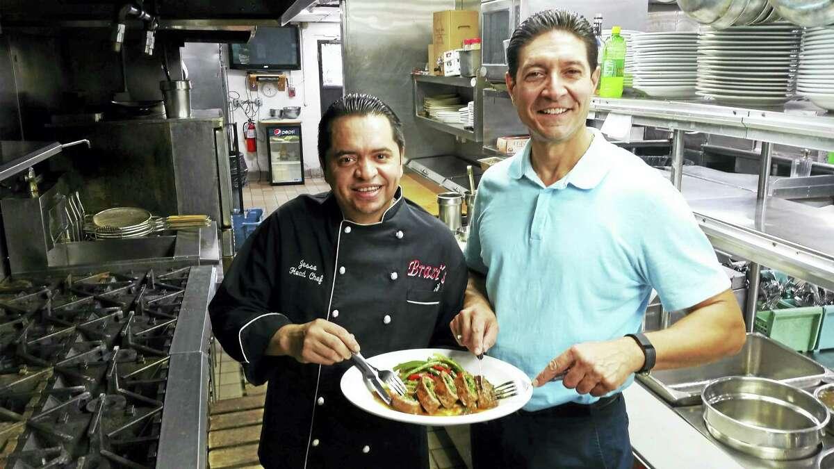 Brazi's Italian Restaurant Chef Jesse Melgar and owner Val Capobianco holding the restaurant's newest dish The Justice Harper Steak Rollatini.