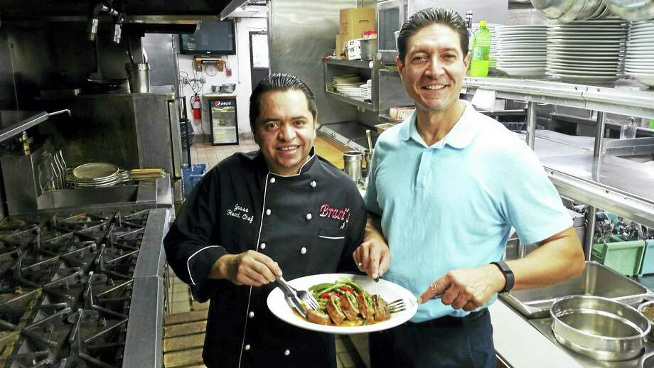 Brazi's Italian Restaurant Chef Jesse Melgar and owner Val Capobianco holding the restaurant's newest dish The Justice Harper Steak Rollatini. Photo: Shahid Abdul-Karim — New Haven Register