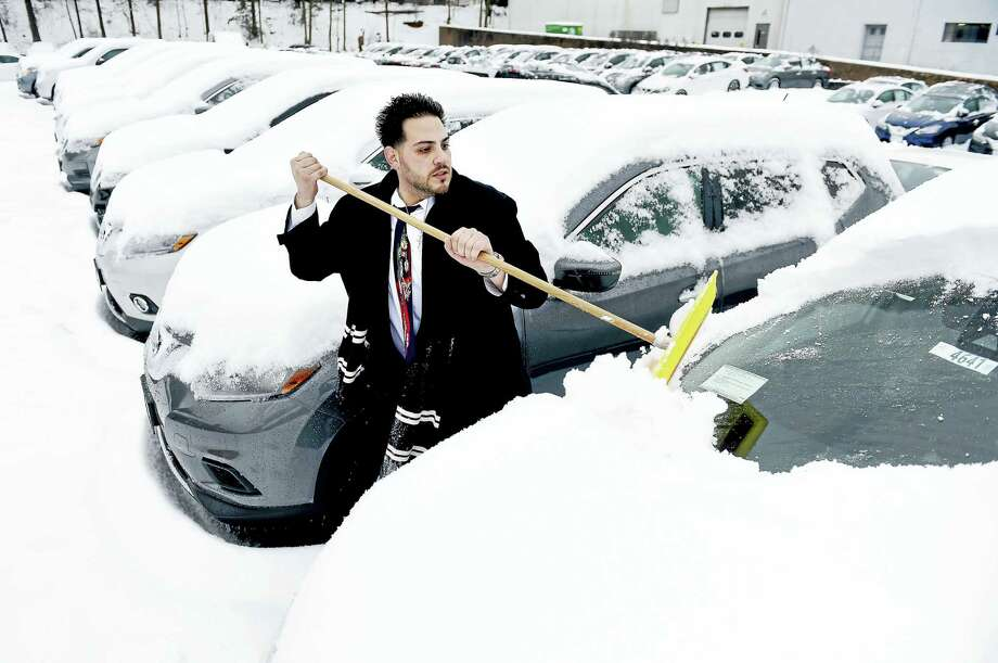 Salesman Cesar Barbagallo clears the snow off of new cars at George Harte Nissan in West Haven on 12/17/2016. Photo: Arnold Gold-New Haven Register