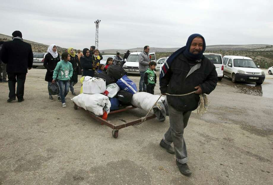 A Syrian man pulls their belongings after he was evacuated with his family from Aleppo, near Idlib, Syria, Friday, Dec. 16, 2016. Turkey's Foreign Minister Mevlut Cavusoglu says 7,500 civilians have been evacuated from the Syrian city of Aleppo and that he has reached out to Tehran in a bid to keep the process on track. Photo: AP Photo / Copyright 2016 The Associated Press. All rights reserved.