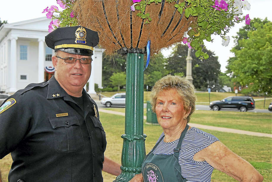 Branford Police Chief Kevin Halloran and Garden Club member Eunice Lasala hang blue ribbons Monday on the 32 flower baskets that line downtown Main Street. Photo: CONTRIBUTED PHOTO — Bill O'Brien