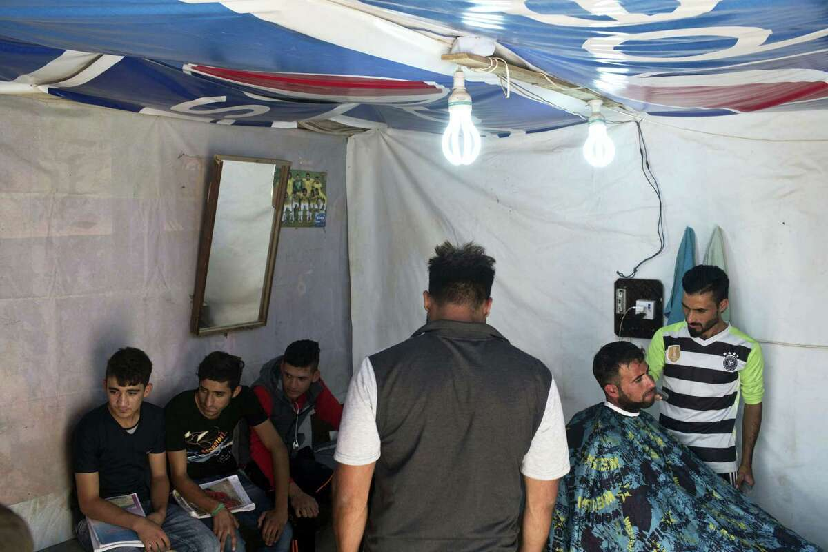 A customer gets his beard trimmed at a makeshift barbershop inside the Baharka camp for displaced persons on the outskirts of Irbil, Iraq, Tuesday, Oct. 25, 2016. Nearby Mosul, the largest city controlled by the Islamic State group, is still home to more than 1 million civilians. The government and international aid groups fear that a sudden mass exodus will overwhelm the few camps set up on its outskirts.