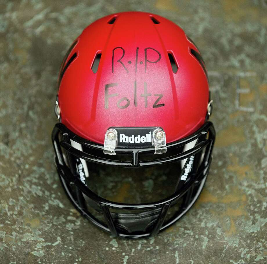 """A Nebraska mini-football helmet inscribed """"RIP Foltz,"""" for Nebraska punter Sam Foltz is seen during a vigil for Foltz, Sunday in Lincoln, Neb. Foltz and former Michigan State punter Mike Sadler died in a car crash in Wisconsin after working at a kicking clinic. Photo: Francis Gardler — The Journal-Star Via AP   / The Journal-Star"""