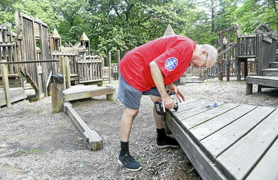 Dan Scinto of the Derby Lowe's store removes a board on the playground at Painter Park in West Haven Friday. Photo: Arnold Gold — New Haven Register