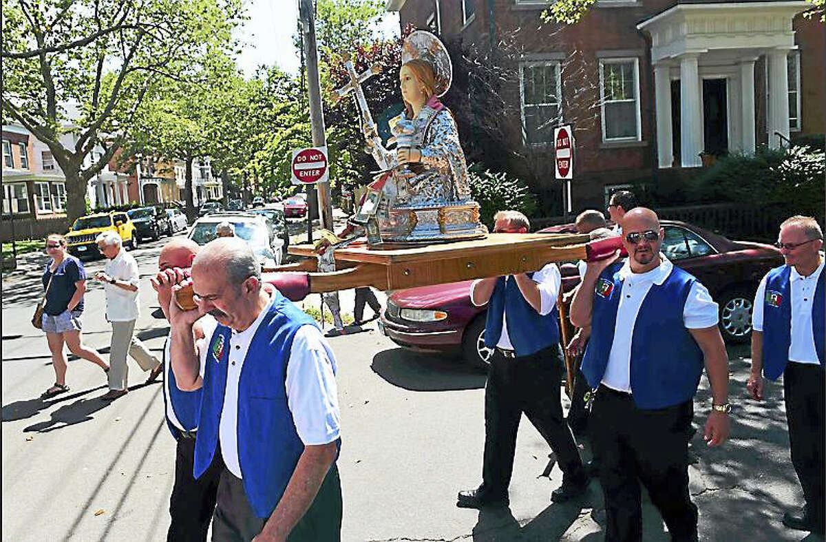 The Santa Maria Maddalena Society in New Haven celebrates its 118th anniversary with its annual Old World procession Sunday as society members carry the statue of St. Maria Madalena, the patron saint of Atrani, Italy, through the streets of Wooster Square.
