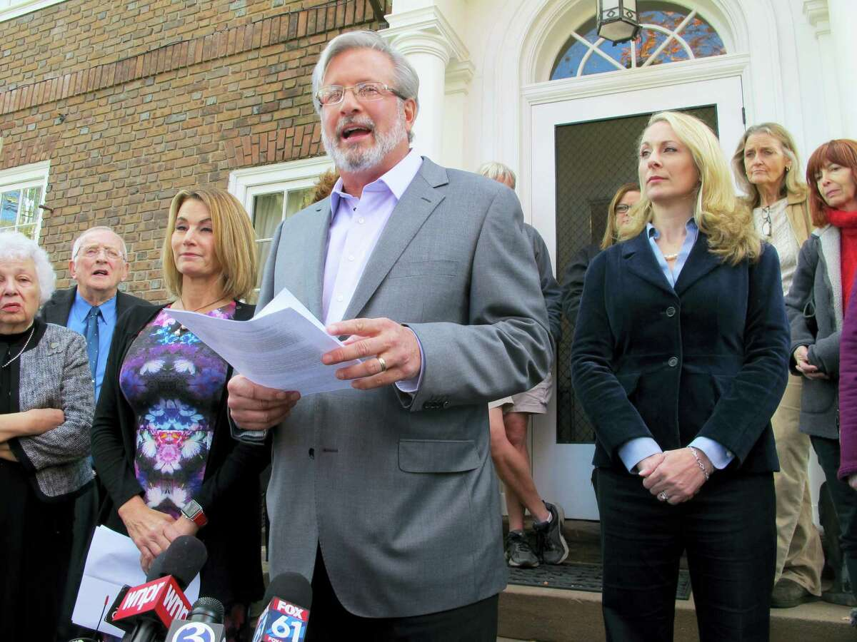Connecticut state House candidate Dr. William Petit Jr., flanked by House Minority Leader Themis Klarides, R-Derby, left, and his wife, Christine, right, speaks to the news media Wednesday in Plainville about a political advertisement linking him to Donald Trump and attacks on women and families.