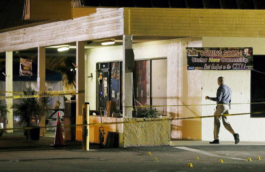 An investigator walks near the scene of a fatal shooting at Club Blu nightclub in Fort Myers, Fla. on July 25, 2016. Photo: Kinfay Moroti/The News-Press Via AP   / The News-Press
