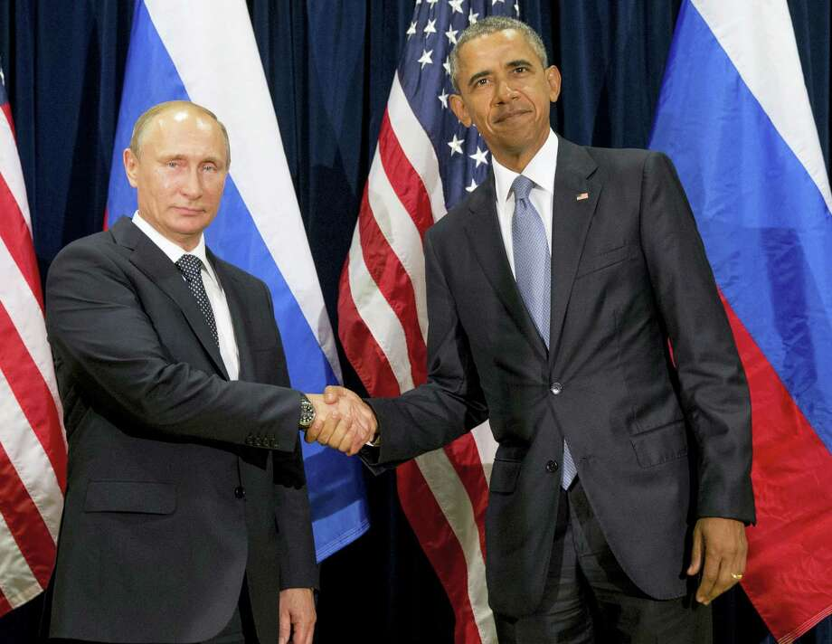 U.S. President Barack Obama, right, and Russia's President Vladimir Putin pose for members of the media before a bilateral meeting at the United Nations headquarters. President Barack Obama is promising that the U.S. will retaliate against Russia for its suspected meddling in America's election process, an accusation the Kremlin has vehemently denied. Photo: Andrew Harnik — AP File Photo / Copyright 2016 The Associated Press. All rights reserved.