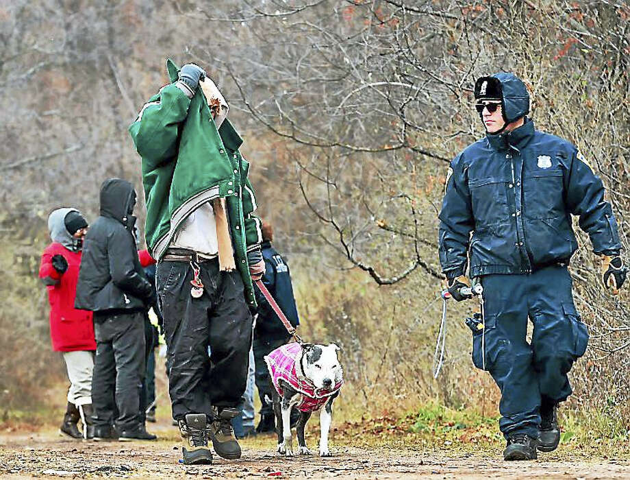 A homeless man with his dog, New Haven Police and city officials leave a New Haven homeless encampment off of I-91 exit 6, near the Mill River before it was razed Thursday. Residents of the camp were ordered by the City of New Haven last week to leave the encampment. Photo: Peter Hvizdak — New Haven Register