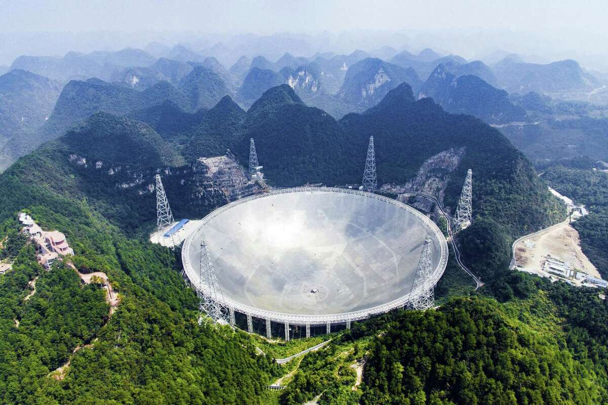 In this Sept. 24, 2016 photo released by Xinhua News Agency, an aerial view shows the Five-hundred-meter Aperture Spherical Telescope (FAST) in the remote Pingtang county in southwest China's Guizhou province. China has begun operating the world's largest radio telescope to help search for extraterrestrial life.
