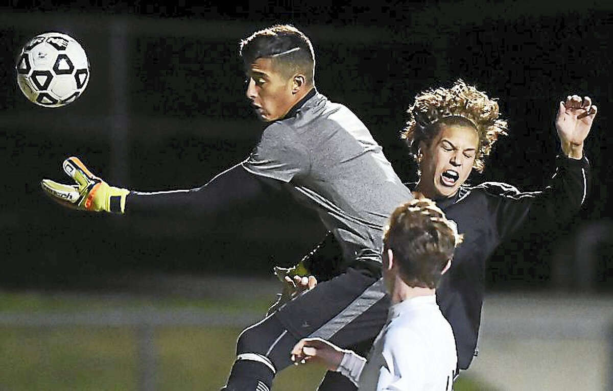 Hand senior Jackson Guay battles Guilford keeper Orlando Diaz in a 1-0 win Monday for the Tigers at the James W. Kavanaugh Athletic Complex at Guilford High School.