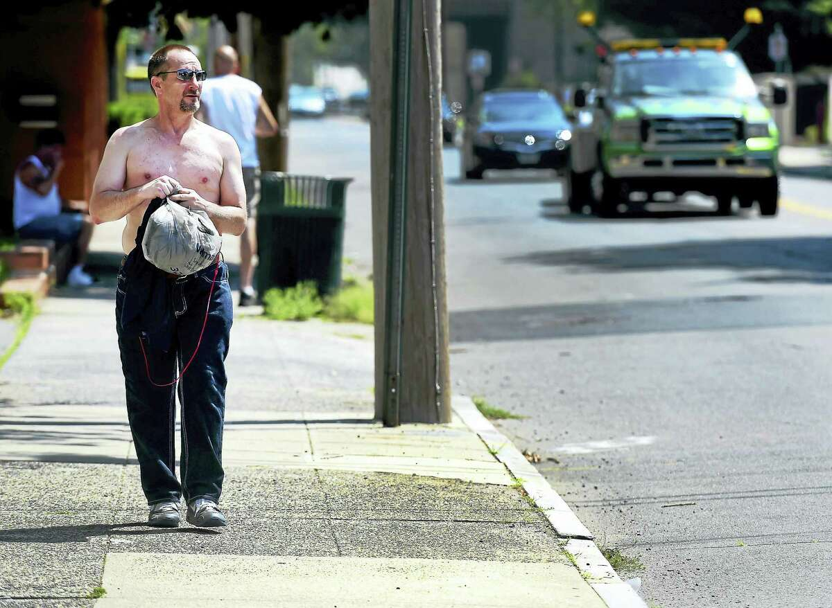 City resident Mike Lucher tries to stay cool as he walks on Grand Avenue in New Haven