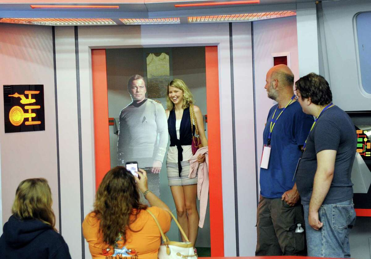 """AP Photo/Hans Pennink In this Saturday, Aug. 13, 2016, photo, Kara Benoit of Frederick, Md., poses for a photograph with a cardboard cutout of Capt. James T. Kirk in the turbo lift entrance to the bridge of the replica starship Enterprise during the Trekonderoga festival in Ticonderoga, N.Y. Sets mimicking those of the 1960s TV series """"Star Trek"""" have become a tourist attraction in upstate New York."""