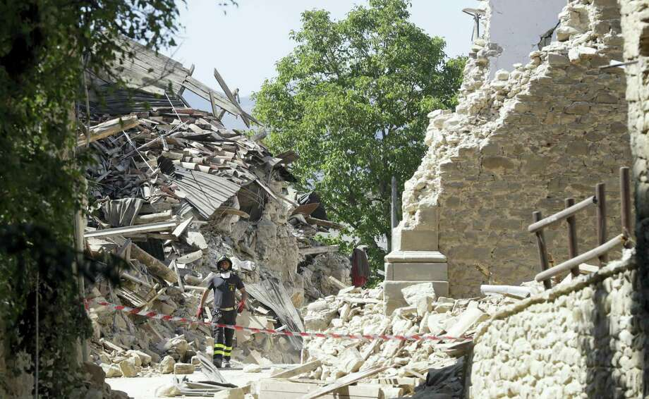 A firefighter stands by a cordoned off area in Amatrice, central Italy, Thursday, Aug. 25, 2016, where a 6.1 earthquake struck just after 3:30 a.m., Wednesday. Rescue crews raced against time Thursday looking for survivors from the earthquake that leveled three towns in central Italy and Italy once again anguished over how to secure its towns and cities, new and old, built on seismic lands. Photo: AP Photo/Alessandra Tarantino    / Copyright 2016 The Associated Press. All rights reserved. This material may not be published, broadcast, rewritten or redistribu