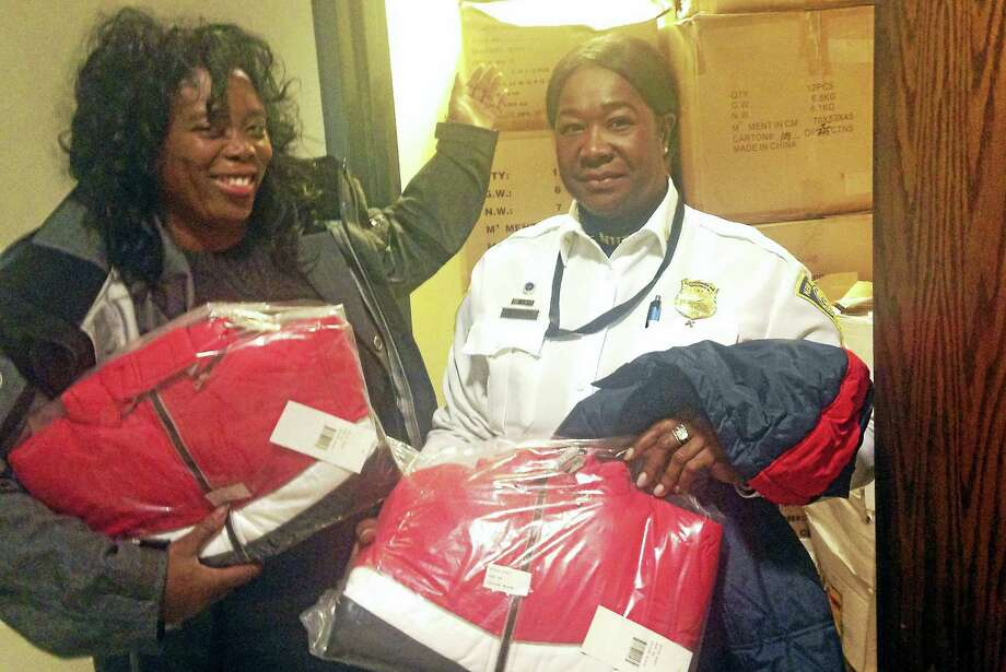 Metashar Dillon, CEO of the Kingdom International Economic Development Corporation (right) and New Haven police Capt. Patricia Helliger get ready to transport 1,000 coats to the 2016 KIEDC Christmas Holiday Toy, Coat, Hat & Food Drive. Photo: Digital First Media