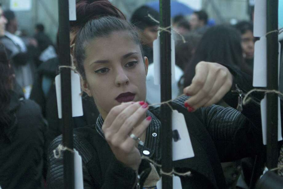 A woman hangs a tag on bars representing a prison cell during protest against human trafficking in Madrid, Spain on Oct. 22, 2016. Police in Spain say they have arrested 21 people and freed four women while breaking up an alleged human trafficking ring Saturday in the southern city of Malaga after a victim called the national anti-sex trafficking hotline saying she was being forced into prostitution and to consume illegal drugs. Photo: AP Photo/Paul White   / Copyright 2016 The Associated Press. All rights reserved.