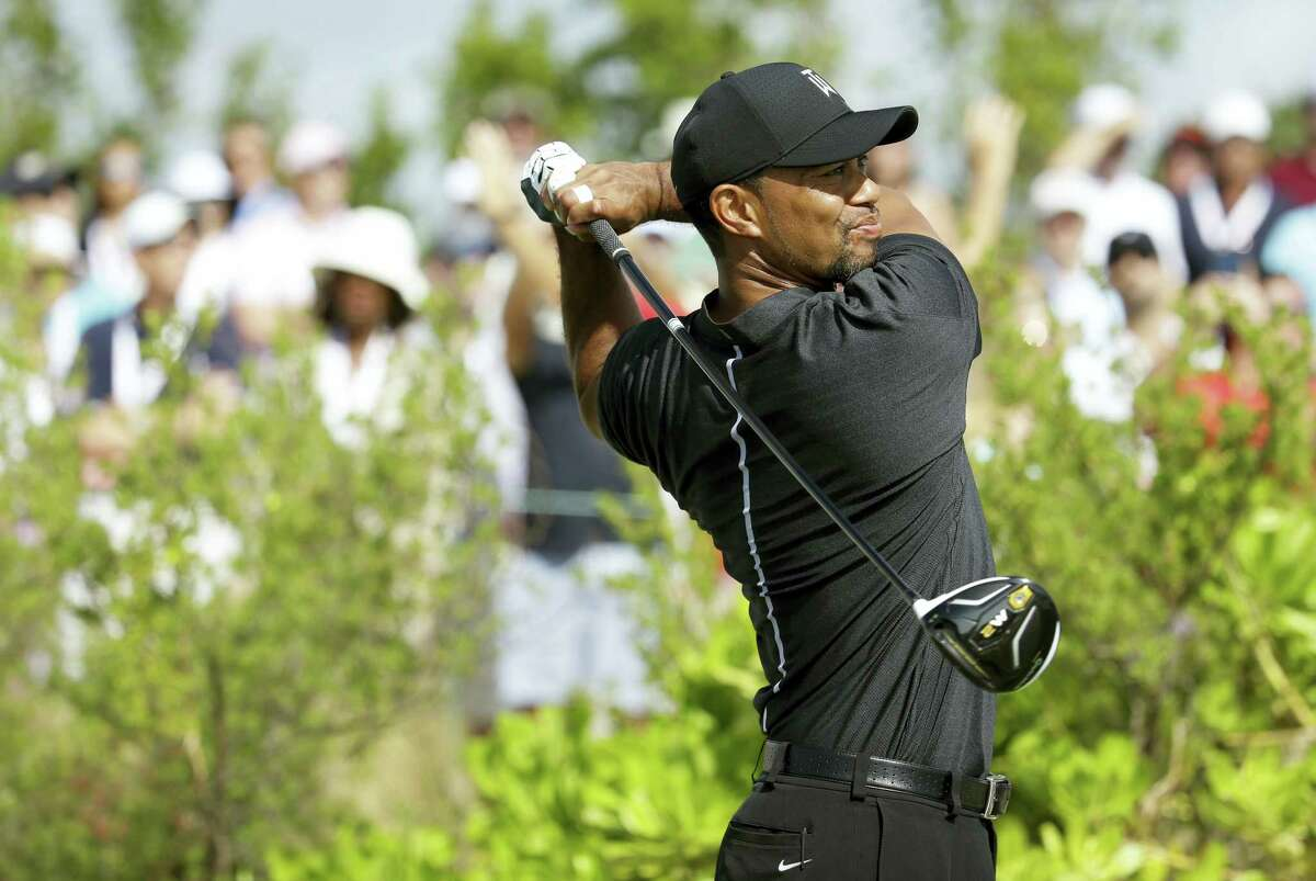 Tiger Woods watches his tee shot during the first round at the Hero World Challenge golf tournament in Nassau, Bahamas.
