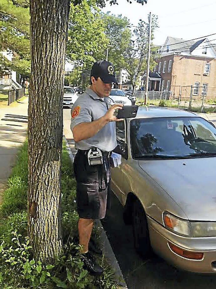 MARY O'LEARY - NEW HAVEN REGISTERParking enforcement officer Stephen Saladino tickets someone parked in a residential zone without a permit. Photo: Journal Register Co.