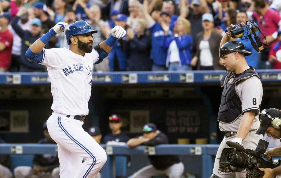 Jose Bautista, left, celebrates his three-run home run in front of Yankees catcher Brian McCann on Saturday. Photo: Mark Blinch — The Canadian Press Via AP   / The Canadian Press