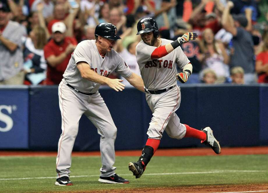 Third base coach Brian Butterfield, left, congratulates Dustin Pedroia after Pedroia's grand slam on Saturday. Photo: Steve Nesius — The Associated Press   / FR69810 AP