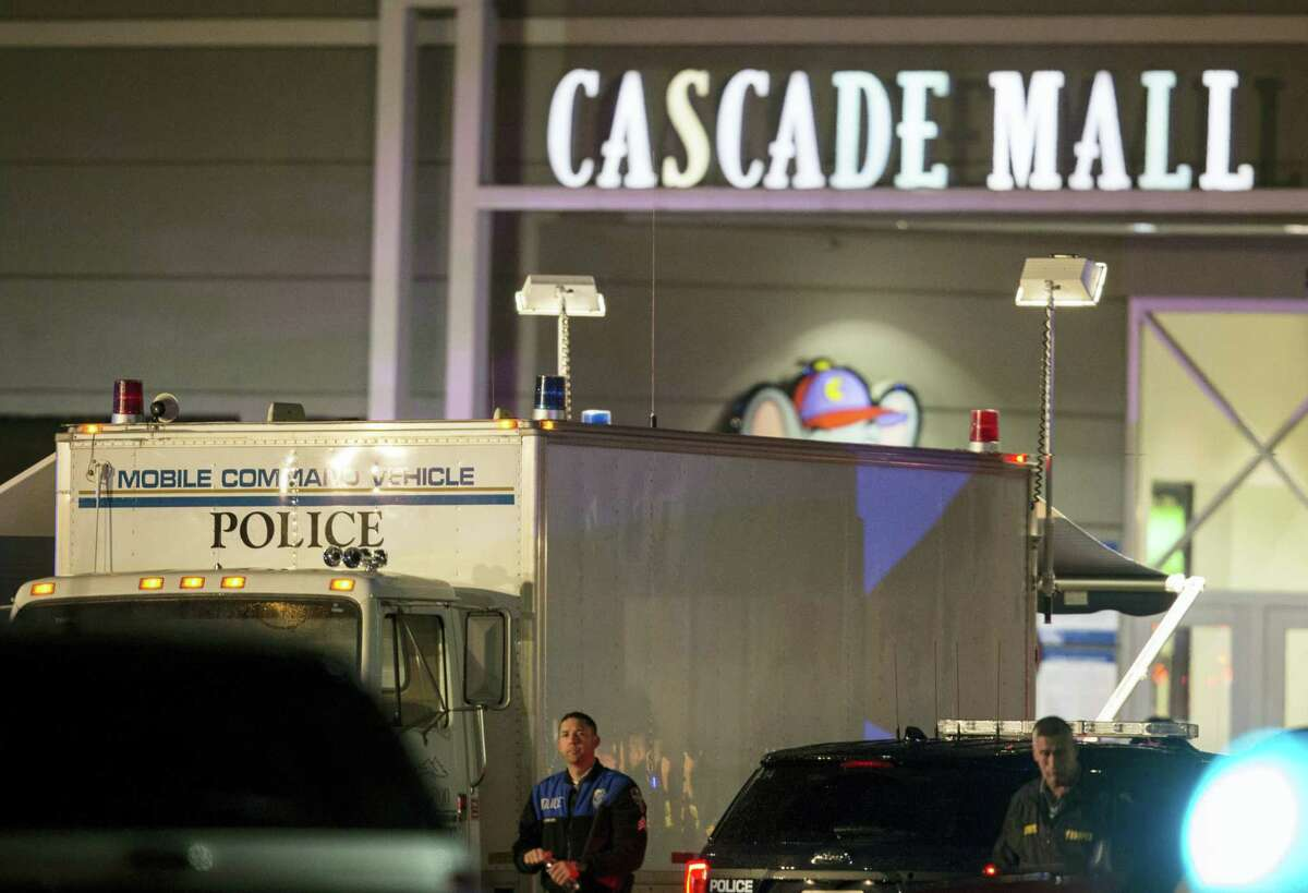 Law enforcement officers stand near a mobile police command center at the scene of a shooting where several people were killed Friday, Sept. 23, 2016, in Burlington, Wash. Police searched Saturday for a gunman who opened fire in the makeup department of a Macy's store at the mall north of Seattle, killing several females, before fleeing toward an interstate on foot, authorities said.