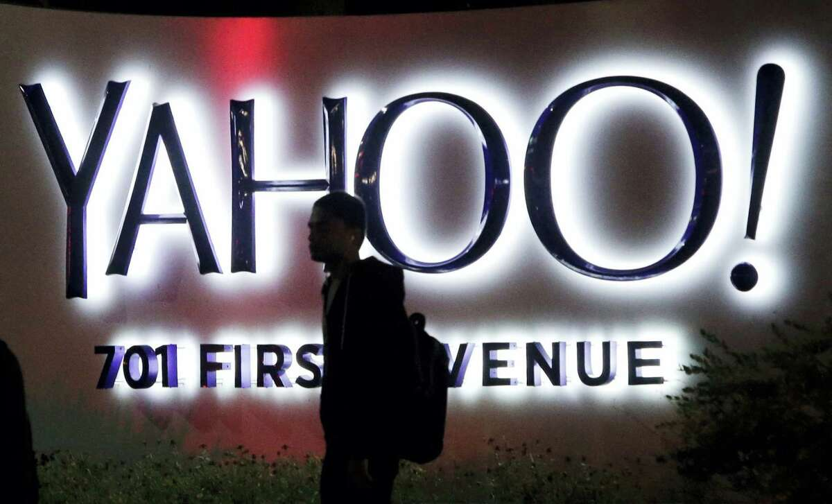 In this Nov. 5, 2014 photo, a person walks in front of a Yahoo sign at the company's headquarters in Sunnyvale, Calif.