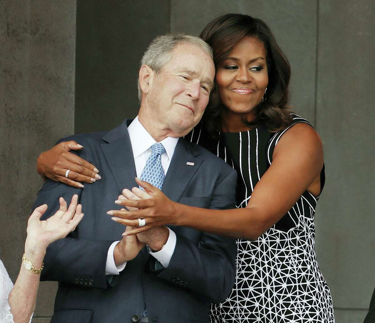 First lady Michelle Obama hugs former President George W. Bush during the dedication ceremony for the Smithsonian Museum of African American History and Culture on the National Mall in Washington, Saturday, Sept. 24, 2016.