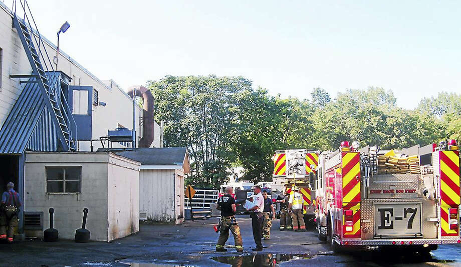 Employees were evacuated and part of the Boston Post Road in Milford was shut down for a short time Wednesday morning as firefighters put out a smoldering roof fire at Drill Masters Eldorado Tool, 336 Boston Post Road. There were no injuries. Photo: Wes Duplantier — The New Haven Register