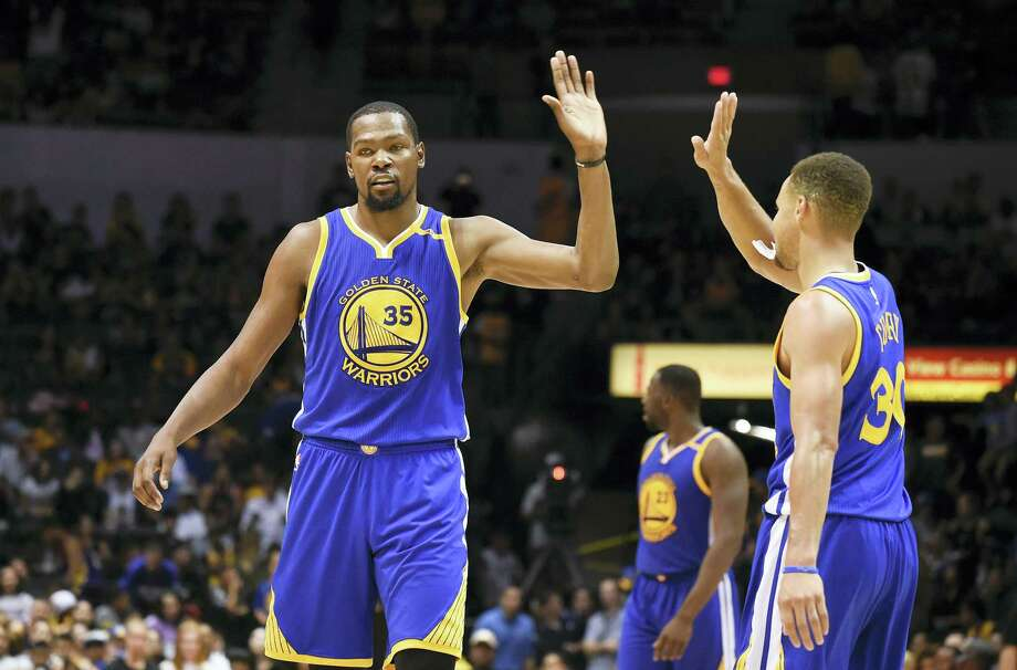 Golden State Warriors forward Kevin Durant, left, high-fives Stephen Curry during a preseason game. Photo: Denis Poroy — The Associated Press   / FR59680 AP